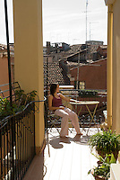Taylor, teenage girl, enjoys the morning sun on the deck overlooking the rooftops of Venice, Italy.