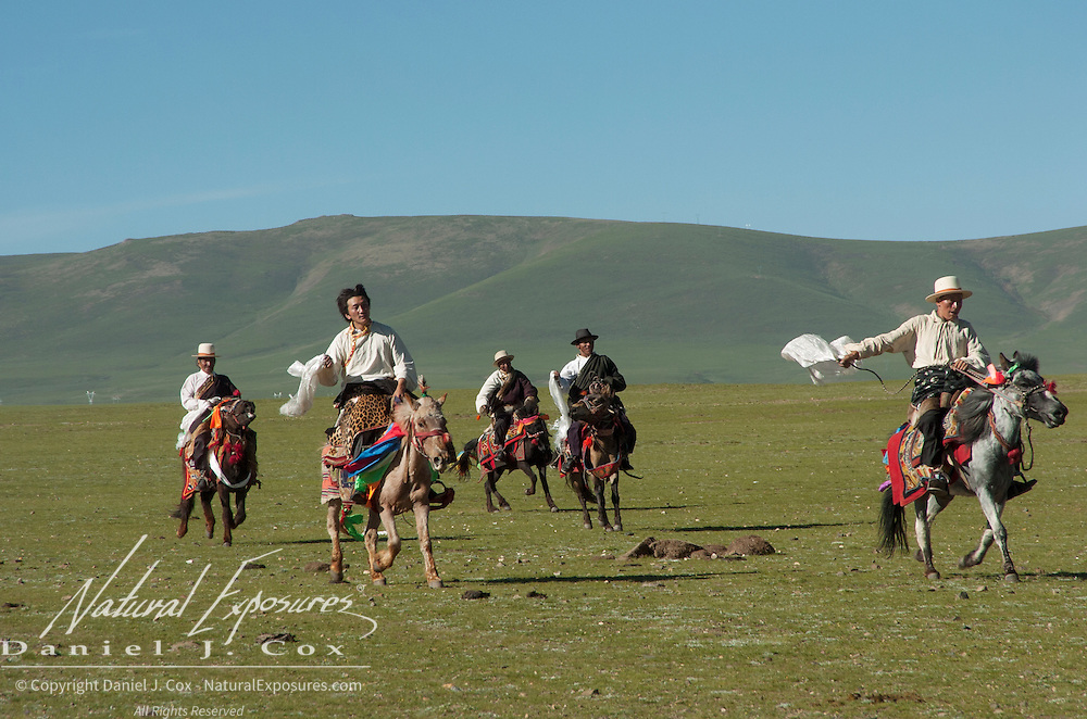 Northern Tibetans in traditional herdsmen dress with decorated horses. Tibet, Asia<br /> EDITORIAL USE ONLY - MODEL RELEASES N/A