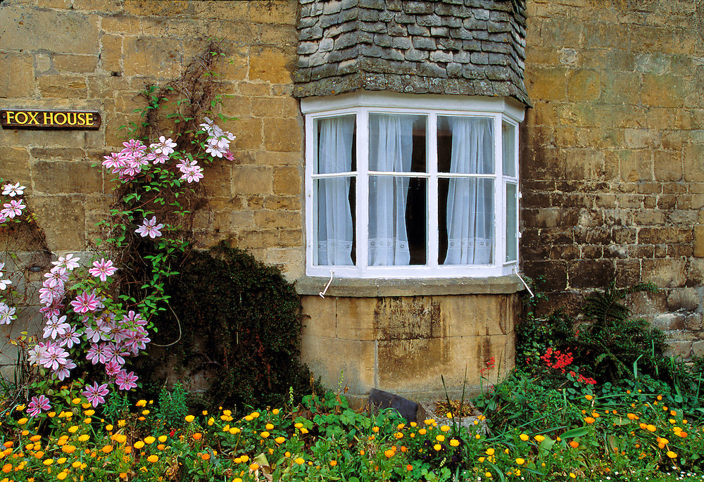 Bright flowers and a white-paned window contrast with the golden stone walls of Fox House, in Broadway in the Cotswolds, England.