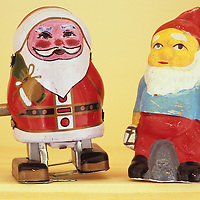 Wind-up tin model of Father Christmas with mechanical legs standing on narrow shelf next to papier mache gnome with lantern