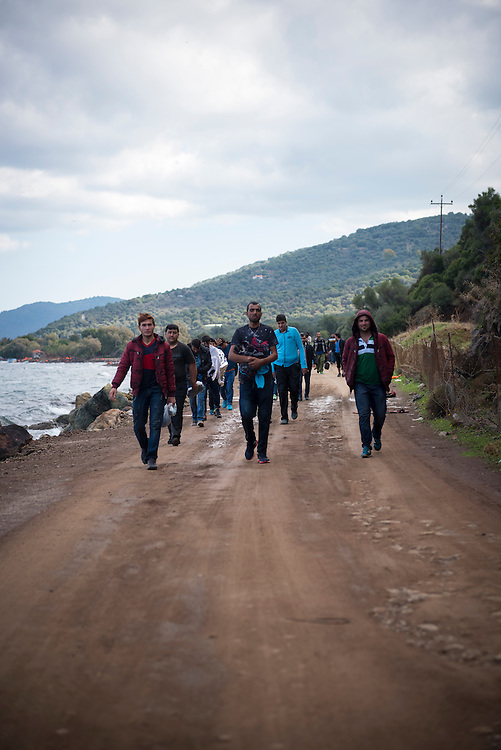 On the northern coast of the Greek island of Lesbos, between the town of Molyvos and village of Skala Skamnias, groups of migrants who have just arrived by boat from Turkey walk along a dirt road toward a registration center several kilometers away.