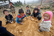 "Hilltribe villages around Sapa. Black Hmong kids playing with ""cars""."