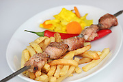 Char grilled turkey Shish Kebab Skewer with french fries and chilli