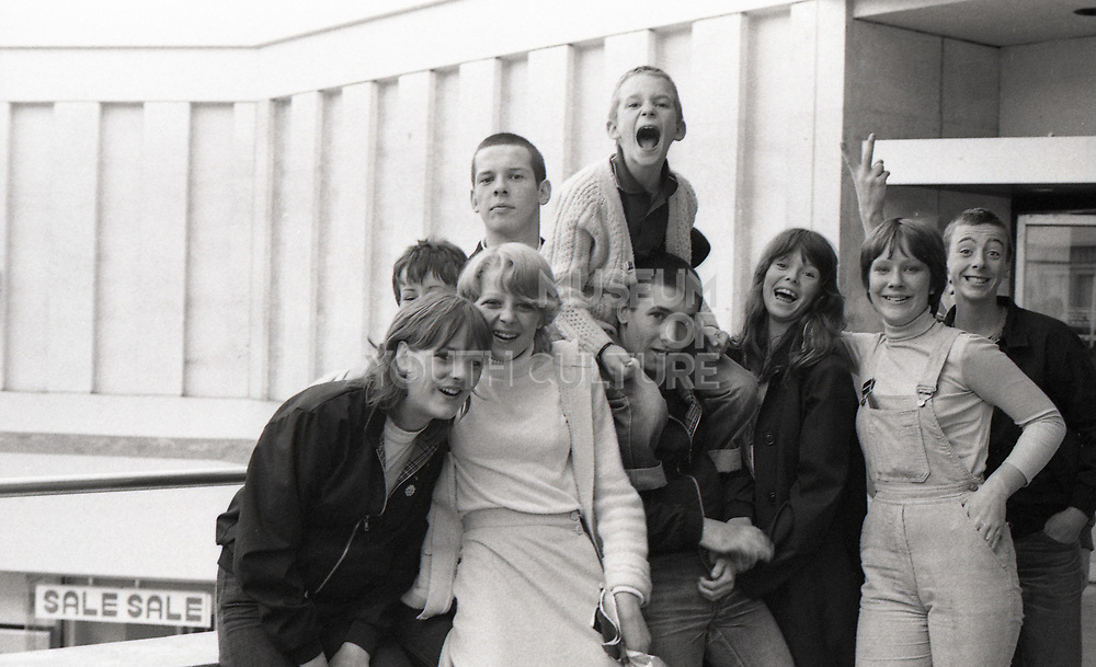 Symond and Neville with friends by shops, UK, 1980s.