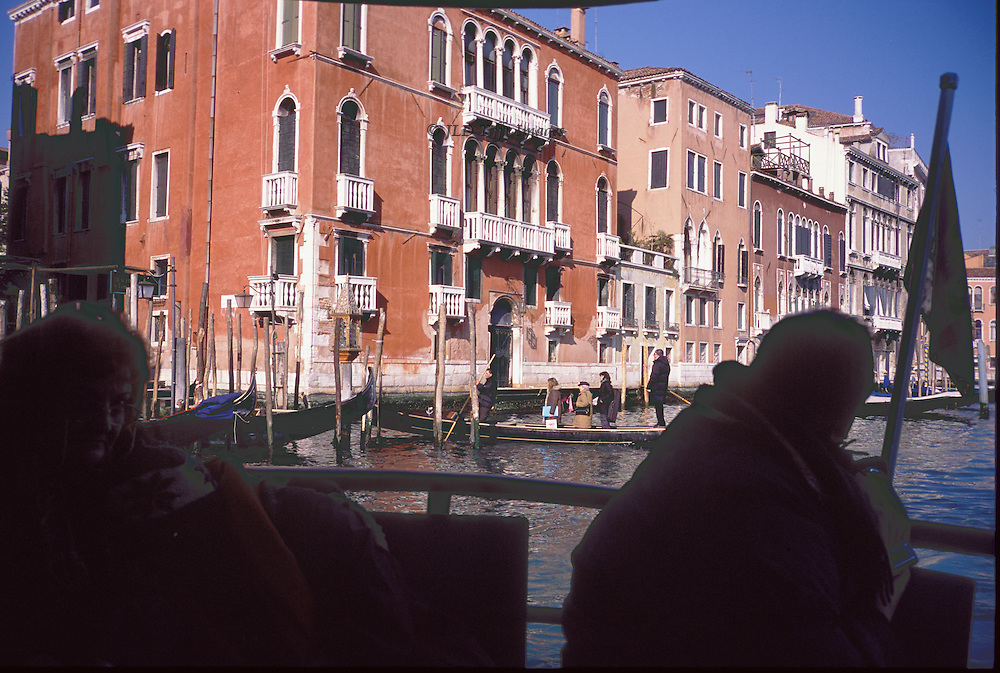 Riding a vaporetto on the Grand Canal, from the deck.  Silhouettes of two other passengers in the foreground; beyond, the canal and a row of palazzi.  Feeling of being there.
