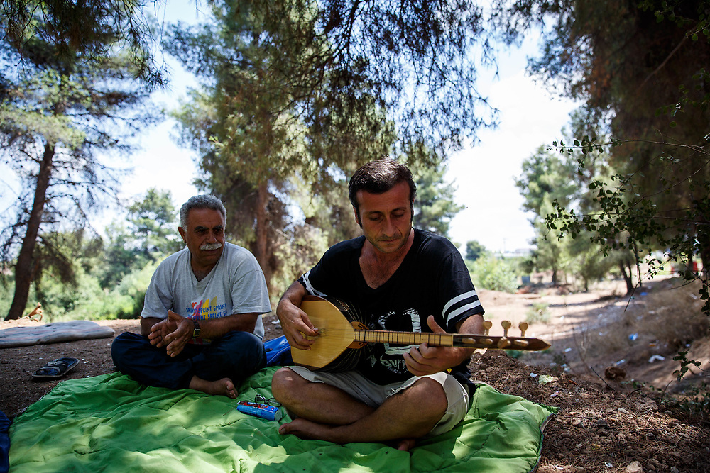 Adnan, 44, a Kurdish Iraqi refugee performing with his Kurdish Syrian friend, Duju. Ritsona Refugee Camp, Greece, July 2016.