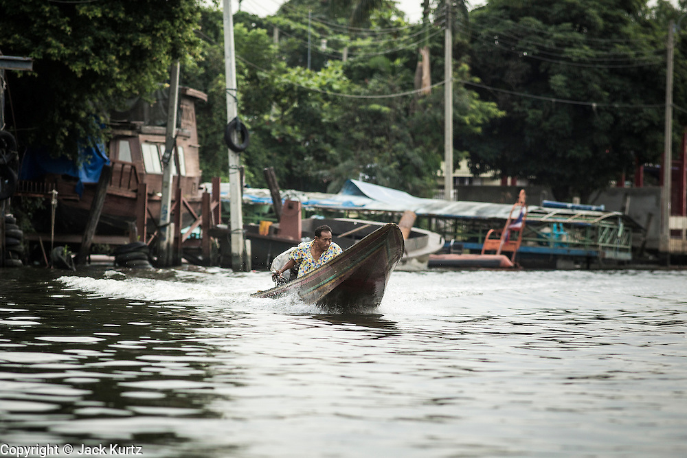 "17 NOVEMBER 2012 - BANGKOK, THAILAND:  A man runs his ""long tailed"" boat up a canal in Bangkok. Long tailed boats use big V8 car engines and have 30-40 foot long propeller shafts that extend past the back of the boat. Bangkok used to be known as the ""Venice of the East"" because of the number of waterways the criss crossed the city. Now most of the waterways have been filled in but boats and ships still play an important role in daily life in Bangkok. Thousands of people commute to work daily on the Chao Phraya Express Boats and fast boats that ply Khlong Saen Saeb or use boats to get around on the canals on the Thonburi side of the river. Boats are used to haul commodities through the city to deep water ports for export.    PHOTO BY JACK KURTZ"