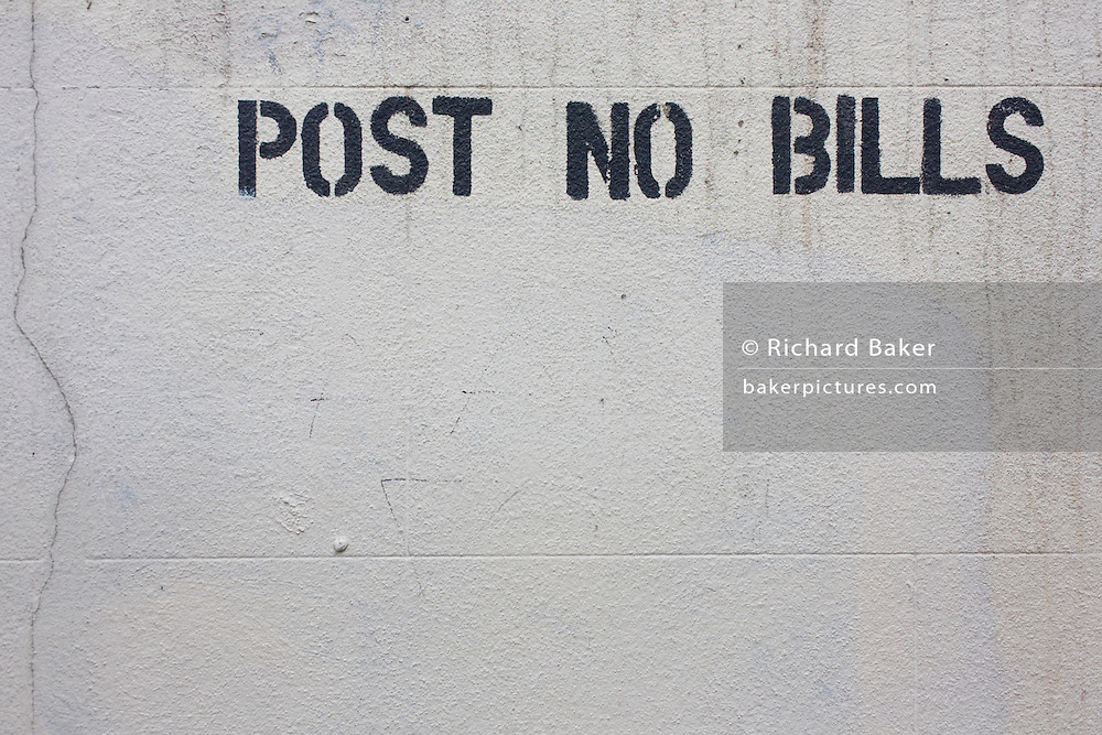 Removed graffiti and 'Post No Bills' stencil on cleaned white wall in central London street.
