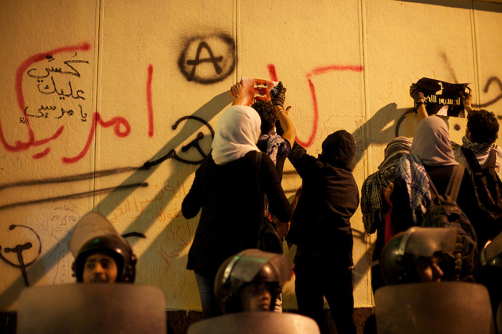 December 11, 2012 - Cairo, Egypt: A group of protestors paint stencils in the wall of the presidential place in Cairo, where tens of thousands gathered to voice their anger at the planned constitution, which will be put to a referendum next Saturday...The Egyptian army has reportedly called talks between President Mohamed Morsi and the opposition to end violent protests against a draft constitution...Sporadic clashes between supporters and opponents of president Mohamed Morsi, erupted in the past week over his assumption of extraordinary powers and the scheduling of the referendum. (Paulo Nunes dos Santos/Polaris)