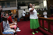 As one of the invited guests of the week, a woman is singing a praise song to God during a Mass Service at the Hip Hop Church in Harlem, New York, NY., on Thursday, July 21, 2006. A new growing phenomenon in the United States, and in particular in its most multiethnic city, New York, the Hip Hop Church is the meeting point between Hip Hop and Christianity, a place where ?God? is worshipped not according to religious dogmatisms and rules, but where the ?Holy Spirit? is celebrated by the community through young, unique, passionate Hip Hop lyrics. Its mission is to present the Christian Gospel in a setting that appeals to both, those individuals who are confessed Christians, as well as those who are not regularly attending traditional Services, while helping many youngsters from underprivileged neighbourhoods to feel part of a community, to make them feel loved and to help them not to give up when problems arise. The Hip Hop Church is not only forward-thinking but it also has an important impact where life at times can be difficult and deceiving, and where young people can be easily influenced for the worst purposes. At the Hip Hop Church, members are encouraged to sing, dance and express themselves in any way that the ?Spirit of God? moves them. Honours to students who have overcome adversity, community leaders, church leaders and some of the unsung pioneers of Hip Hop are common at this Church. Here, Hip Hop is the culture, while Jesus is the centre. Services are being mainly in Harlem, where many African Americans live; although the Hip Hop Church is not exclusive and people from any ethnic group are happily accepted and involved with as much enthusiasm. Rev. Ferguson, one of its pioneer founders, has developed ?Hip-Hop Homiletics?, a preaching and worship technique designed to reach the children in their language and highlight their sensibilities, while bringing forth Christianity. This ?Keep It Real? evangelism style is the centrepiece of Rev. Ferguson?s ministry,