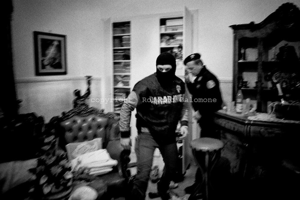 Torre Annunziata, Italia - 10 aprile 2010. Uomini dei Carabinieri in azione all'interno di un'abitazione. I Carabinieri hanno effettuato 11 arresti di soggetti legati ai clan della camorra Gionta e Gallo-Cavaliere durante un blitz a Torre Annunziata (Napoli). Il 'cartello' ha stipulato una pax mafiosa per meglio controllare la zona in cui sta avvenendo un investimento milionario da parte di imprenditori: il polo nautico.<br /> Ph. Roberto Salomone Ag. Controluce<br /> ITALY - Carabinieri forces arrested on April 10, 2010 during a blitz operation 11 people linked to camorra mafia organisation in Torre Annunziata.