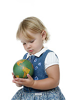 21 July 2008: Two year old toddler Lucy Berg girl with small earth world globe in her hands on a white background in studio.
