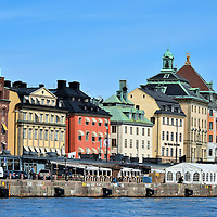 """Row Buildings on Skeppsbron in Stockholm, Sweden <br /> The major waterfront street in Gamla stan is Skeppsbron, which means """"The Ship's Bridge.""""  It is lined with 24 pastel-colored buildings that collectively are called Skeppsbroraden.  This strip of land in Old Town was manmade during the early 17th century to become a quay for docking ships.  By 1854, the current stone walls were finished and the harbor began to be called Skeppsbrokajen.  As the area became prosperous, most of these buildings were constructed during the early 20th century as banks, merchants, warehouses or for other shipping related businesses."""