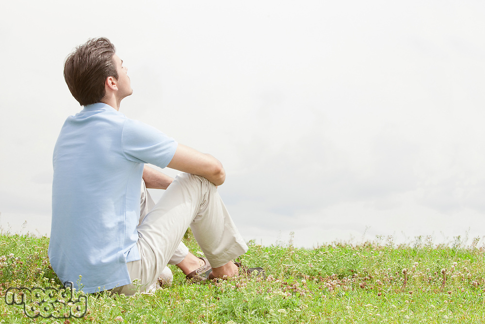 Rear view of relaxed young man sitting on grass against sky