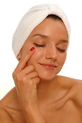 Beautiful woman wearing bath turban, applying eye cream