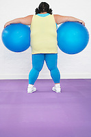 Overweight Woman Holding two Exercise Balls back view