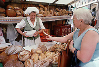 September 1985, Munich, Germany --- A merchant and customer exchange money at a bread stand in a market. --- Image by © Owen Franken/CORBIS