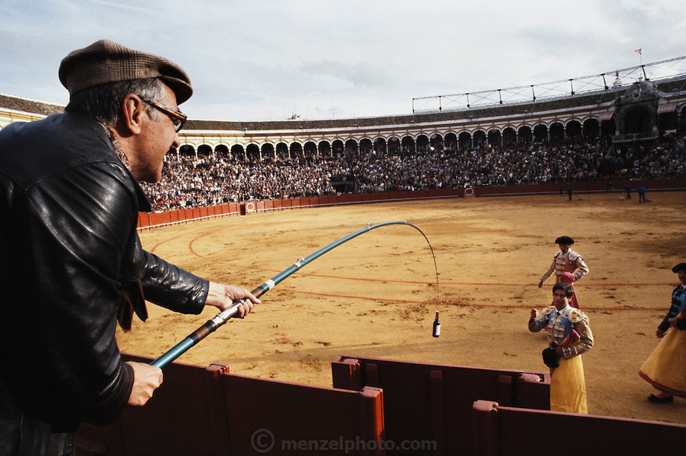 A fan lowers a bottle of wine with a fishing pole to a bullfighter after a very successful fight during April Fair, Seville, Spain.