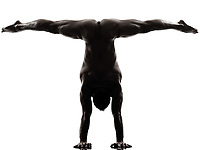one  handsome naked muscular man exercising handstand in silhouette studio on white background
