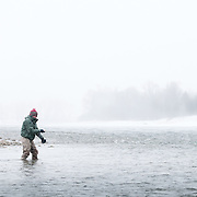 An angler fly fishes for trout during a snow storm on the South Fork of the Snake River, Idaho.
