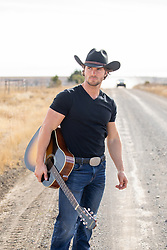hot cowboy with a guitar on a dirt road