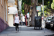 Een meisje loopt door San Francisco. De Amerikaanse stad San Francisco aan de westkust is een van de grootste steden in Amerika en kenmerkt zich door de steile heuvels in de stad.<br /> <br /> A woman is walking in San Francisco. The US city of San Francisco on the west coast is one of the largest cities in America and is characterized by the steep hills in the city.