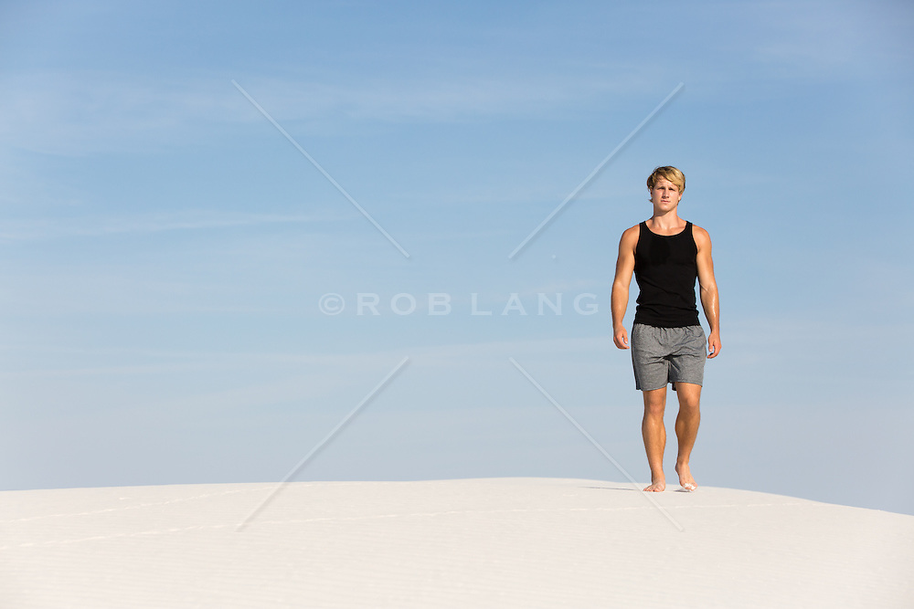 All American athletic man standing on a sand dune in White Sands, NM