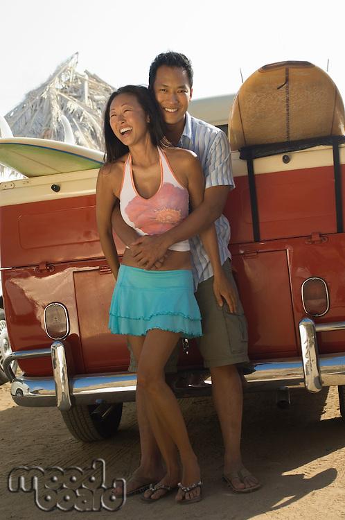 Smiling Surfers Hugging Behind VW Bus