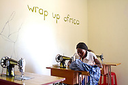 Woman sewing at Wrap Up Africa, Kampala, Africa.  The money she earns will be used for her daughter's chemotherapy.