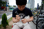 A man shaving the paws of his dog at Banwoldang subway station in the city center of Daegu.
