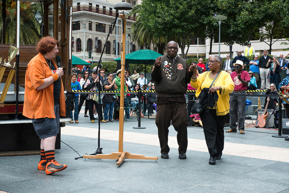 Trini Whittaker is escorted by his Mom to accept his 2nd World Champion Bell Ringing trophy at the 50th Cable Car Bell Ringing Competition in San Francisco's Union Square | July 11, 2013