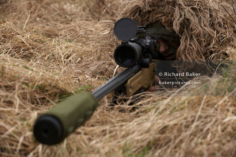 Lying in undergrowth, a camouflaged British infantry soldier is seen squinting down the telescopic sight of the new British-made Long Range L115A3 sniper rifle on Salisbury Plain, Warminster, England. Sniping means concealment, observation and assassination, a strategy the British are using more against the Taliban in Afghanistan. Swiss Lapua .338 inch rounds (8.59mm) travel at sub-sonic speeds of 936 metres/sec, finding its target accurately up to 1,100 metres. The rifle weighs 6.8kg with telescopic image-intensified scopes to 25x life size vision, made by Schmidt & Bender. Front-mounted 'suppressor' minimises the signature normally compromising snipers' position. At £23,000 each, a £4 million contract has been awarded to Accuracy International, to provide the Army, Royal Marines and RAF. The British say this is the best sniper rifle in the world.