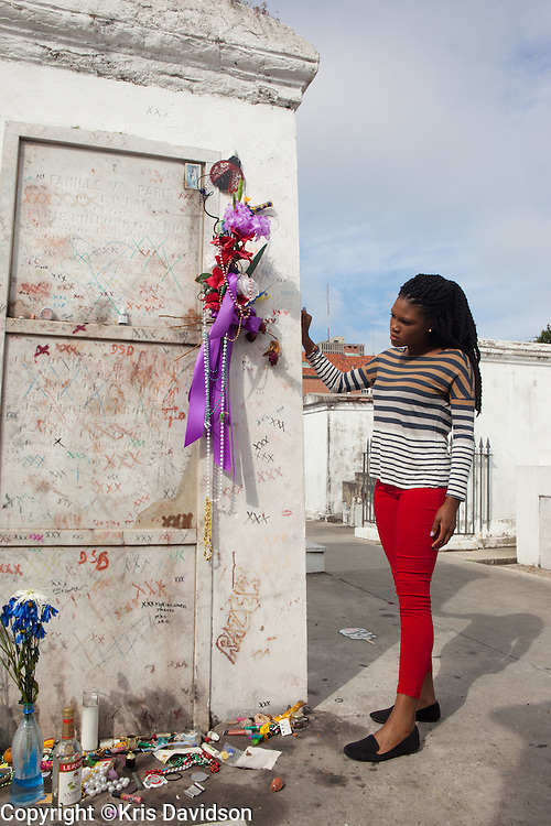 "New Orleans resident Omolola ""Mukondi"" Taiwo visits Marie Laveau's tomb at the St. Louis #1 Cemetery. In the nineteenth century, Voodoo Queen Marie Laveau was the single most storied figure in the substantial New Orleans Voodoo world. To this day, her tomb is the object of adoration and the site of Voodoo offerings -- according to voodoo lore, by knocking three times and silently stating a request, the visitor can appeal to Marie Laveau to grant wishes."