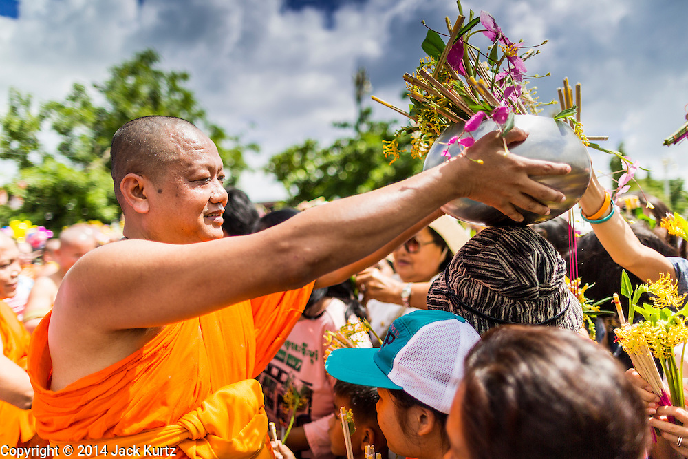 """12 JULY 2014 - PHRA PHUTTHABAT, SARABURI, THAILAND: Monks receive flowers the Buddhist faithful during the Tak Bat Dok Mai at Wat Phra Phutthabat in Saraburi province of Thailand. Wat Phra Phutthabat is famous for the way it marks the beginning of Vassa, the three-month annual retreat observed by Theravada monks and nuns. The temple is highly revered in Thailand because it houses a footstep of the Buddha. On the first day of Vassa (or Buddhist Lent) people come to the temple to """"make merit"""" and present the monks there with dancing lady ginger flowers, which only bloom in the weeks leading up Vassa. They also present monks with candles and wash their feet. During Vassa, monks and nuns remain inside monasteries and temple grounds, devoting their time to intensive meditation and study. Laypeople support the monks by bringing food, candles and other offerings to temples. Laypeople also often observe Vassa by giving up something, such as smoking or eating meat. For this reason, westerners sometimes call Vassa """"Buddhist Lent.""""    PHOTO BY JACK KURTZ"""