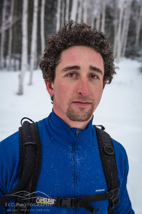 A man takes a break from running on NH 16 in New Hampshire's White Mountains on a snowy winter day.