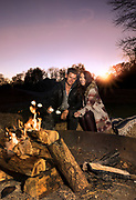 Young couple roasting marshmallows in a campfire.