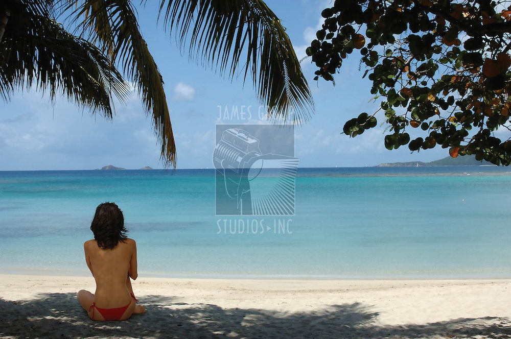 woman sitting on a tropical beach facing the ocean