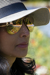 © Licensed to London News Pictures. 04/05/2018. London, UK. Flowers in St James's Park in central London are reflected in the sunglasses of a woman out enjoying the sunshine. High temperatures are expected to continue throughout the bank holiday weekend. Photo credit: Peter Macdiarmid/LNP