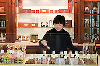 """24 October, 2008. New York, NY. Owner Namhee Girerd Kim, 53, picks an assortment of bon bons and fills a small bag at the boutique """"L'atelier du chocolat"""". The chocolates are made by her husband, Eric Girerd. The stand at the entrance of the shop displays an assortment of chocolate bon bons, including flavors such as herbs. salt, fruit, spices, and classic chocolates.<br /> NOTE: Since no customers were at the shop, the subject posed for the photographer.<br /> ©2008 Gianni Cipriano for The New York Times<br /> cell. +1 646 465 2168 (USA)<br /> cell. +1 328 567 7923 (Italy)<br /> gianni@giannicipriano.com<br /> www.giannicipriano.com"""