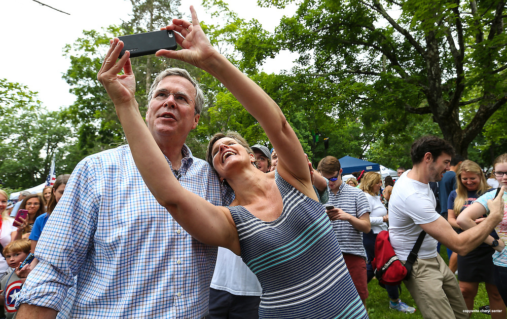 Republican presidential candidate former Florida Gov. Jeb Bush, left, has a selfie taken with a supporter while participating in the Fourth of July Parade festivities in Amherst, N.H.  Saturday, July 4, 2015. (AP Photo/Cheryl Senter)
