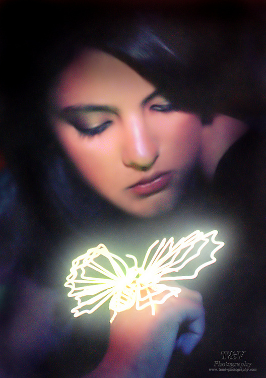 Portrait of a young girl with a glowing butterfly on her hand.Black light