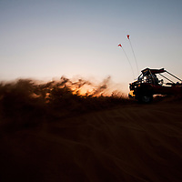 United Arab Emirates, Dubai, Young man driving off-road vehicle at dune bashing site in Al Aweer Desert at sunset