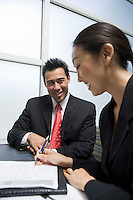 Businesswoman singing agreement with businessman