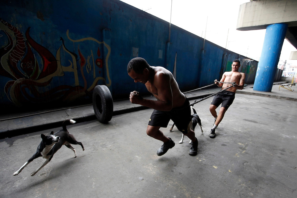 "Aspiring boxers (R-L) Joilson Santos (nicknamed ""Talent""), and Valdir Aparecido (nicknamed ""Gorilla""), use a rope during a training session at a gymnasium under the Alcantara Machado viaduct in the Mooca neighborhood of Sao Paulo, March 25, 2011. The Boxing Academy of Garrido, founded by Brazilian former pro boxer Nilson Garrido, adopts primitive training equipment that he developed himself during his years as a coach, in a project whose goal is to take the sport to the poor and marginalized population."