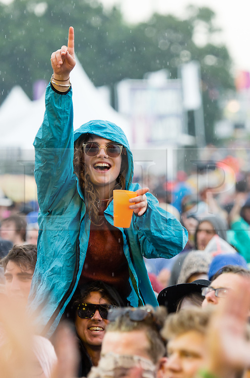 © Licensed to London News Pictures. 12/06/2015. Isle of Wight, UK.  Festival goers dance and listen to music in the pouring rain, as The Struts perform on the main stage, the first band of the day.  Isle of Wight Festival 2015 on Friday Day 2.  Yesterday the weather was hot and Sunny.  Today rain is forecast - the rain started in the bands first2 songs.This years festival include headline artists the Prodigy, Blur and Fleetwood Mac.  Photo credit : Richard Isaac/LNP