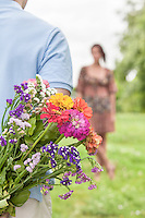 Cropped image of man hiding bouquet from woman in park