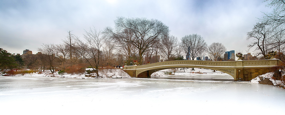 The bow bridge, Central Park, New York in winter with frozen lake and snow.