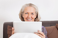 Portrait of happy senior woman with digital tablet at home