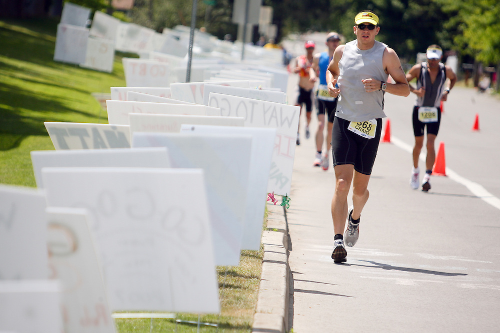 JEROME A. POLLOS/Press..Craig Spreadbury makes his way along Mullan Avenue past hundreds of motivational signs made by family and friends for Ironman participants.
