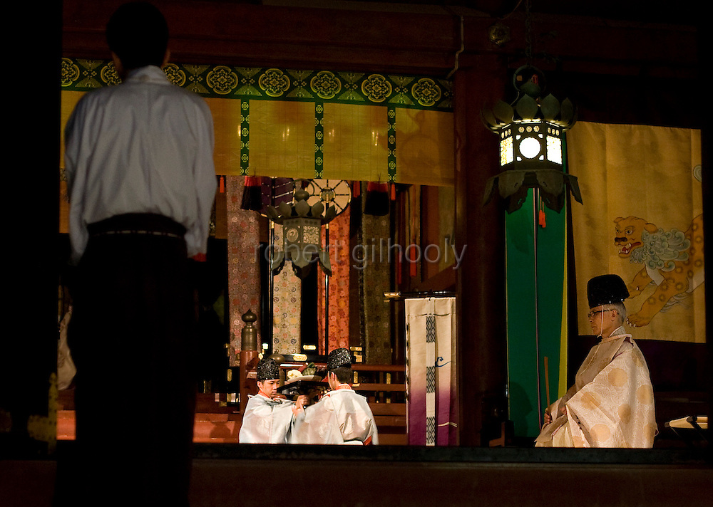 """Priests relay a variety of  goods to be offered to the gods inside the inner sanctuary of the """"Hongu"""" main shrine during a ritual held to announce the start of the annual 3-day Reitaisai grand festival at Tsurugaoka Hachimangu shrine in Kamakura, Japan on  14 Sept. 2012.  Photographer: Robert Gilhooly"""